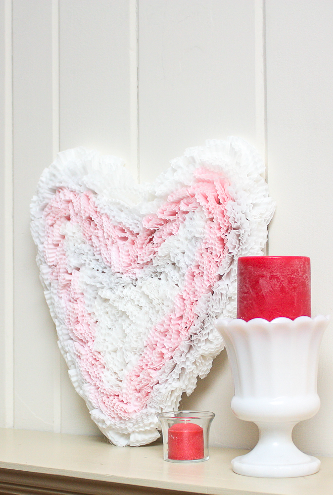Handmade cupcake liner heart displayed on a mantel with dark pink candles in a clear glass votive holder and in a milk glass vase