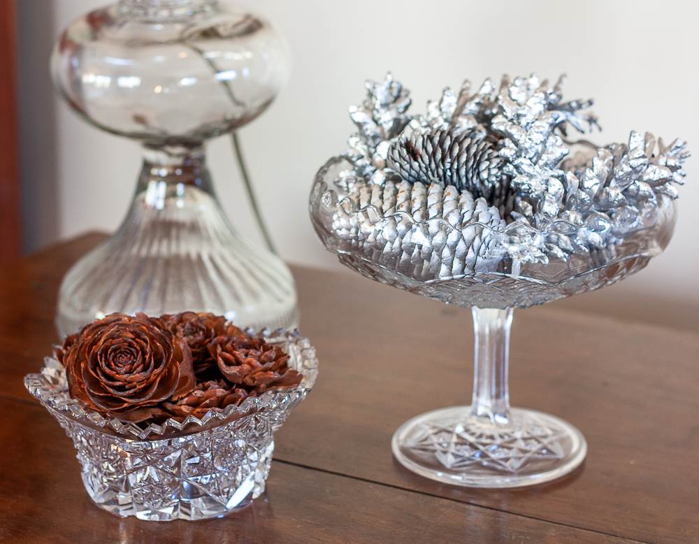 Deodar Cedar cones in a cut glass bowl with a glass compote filled with pine cones painted with silver paint
