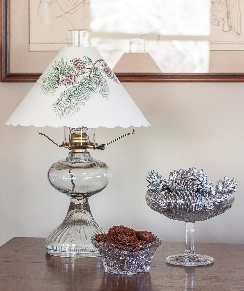 Deodar Cedar cones in a cut glass bowl with a glass compote filled with pine cones painted with silver paint beside an antique oil lamp with a paper shade with pinecones and greenery printed on the shade.