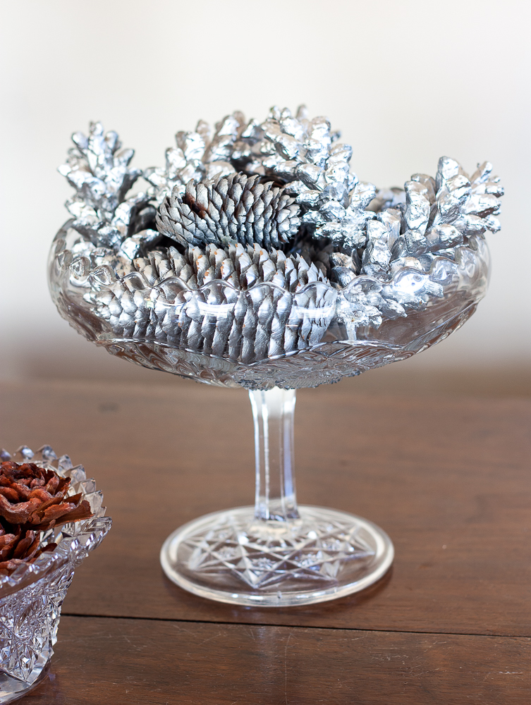 Pinecones painted silver in an antique glass compote