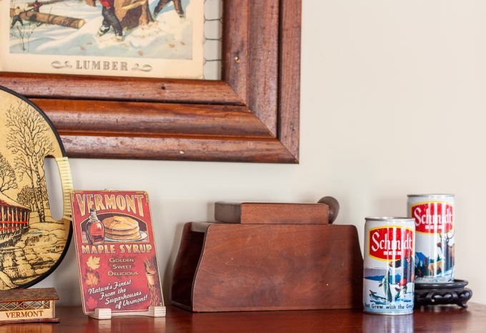 Vintage wood pipe and tobacco holder, 1970s Schmidt beer cans, and a wood Vermont maple syrup postcard