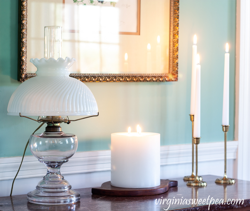 White candles used for winter decor along with an antique oil lamp with a white shade