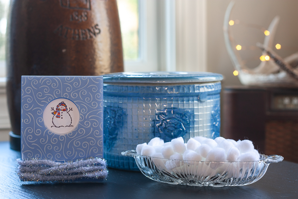 Stamped snowman card, antique blue crock, white pom-poms in a glass bowl