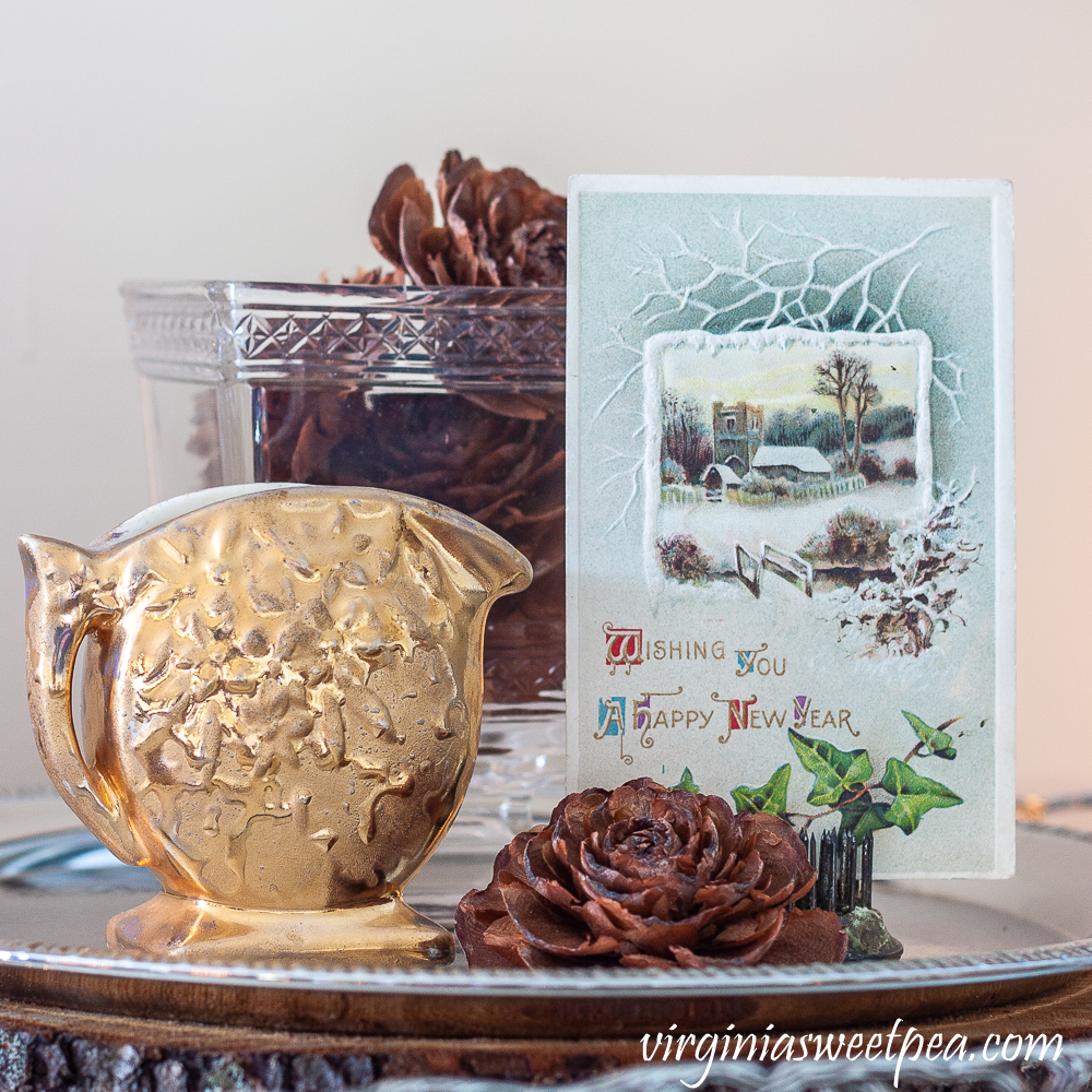 New Year vignette with an antique postcard, gold pitcher, and cones from a Deodar Cedar.