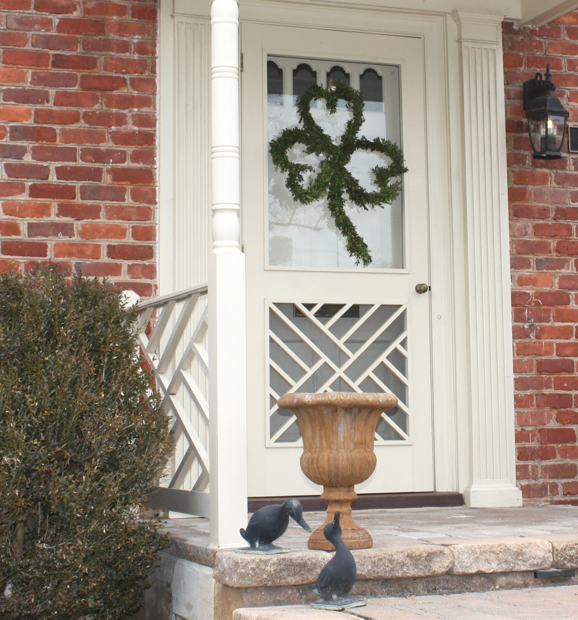 Front door decorated with a Shamrock shaped Boxwood wreath