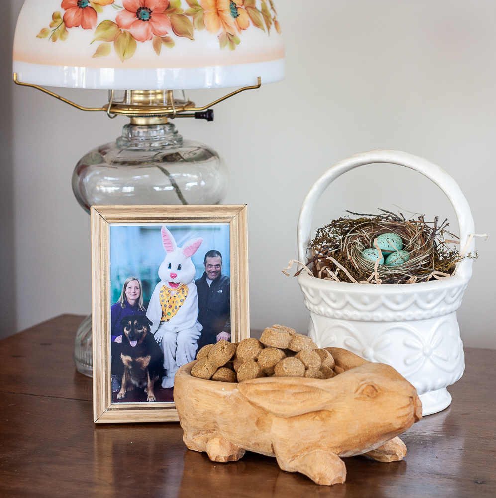 Easter vignette including a family picture with the easter rabbit, carved wood rabbit candy dish, McCoy basket with bird nest, and an oil lamp with a glass shade with flowers on it.