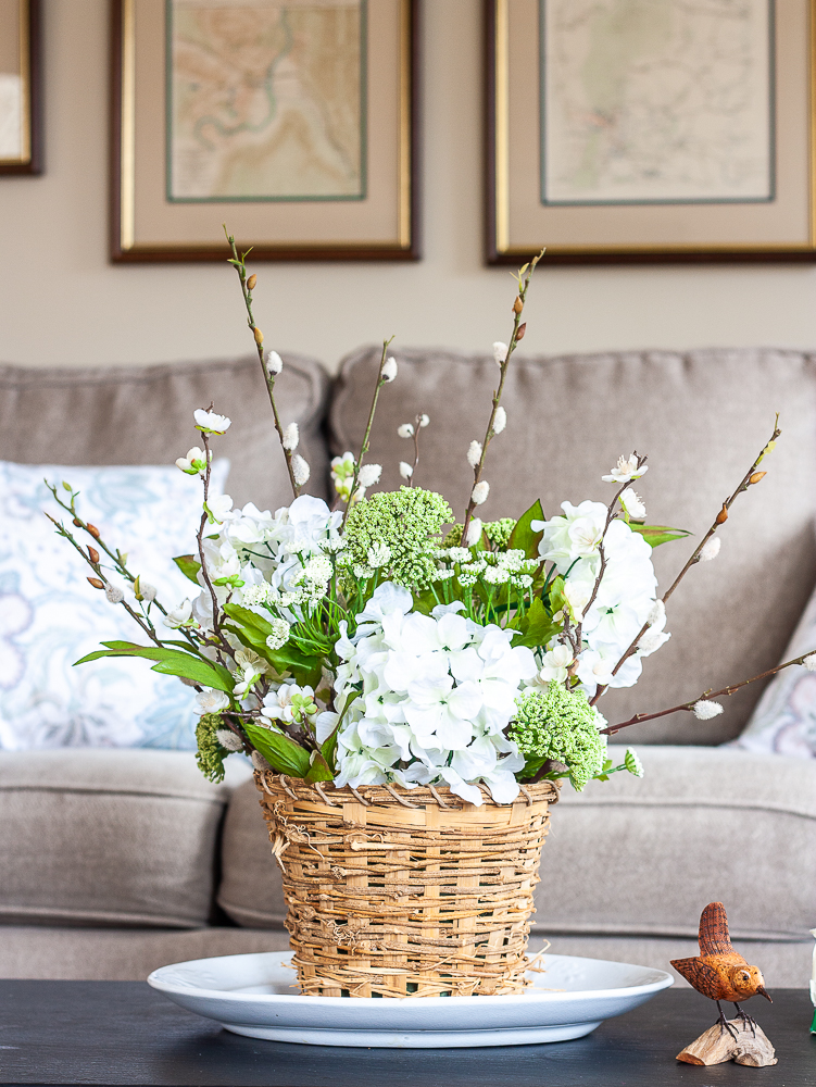 Spring flower arrangement in a woven basket on a coffee table