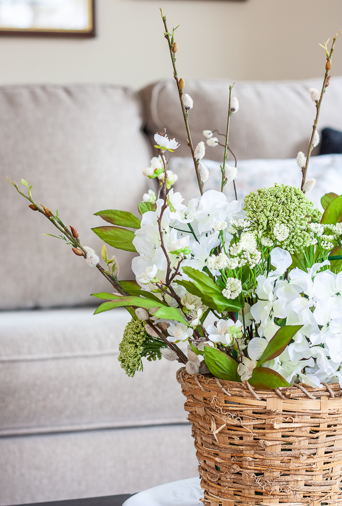 Spring flower arrangement with faux hydrangea, pussy willow, queen anne's lace in a woven basket