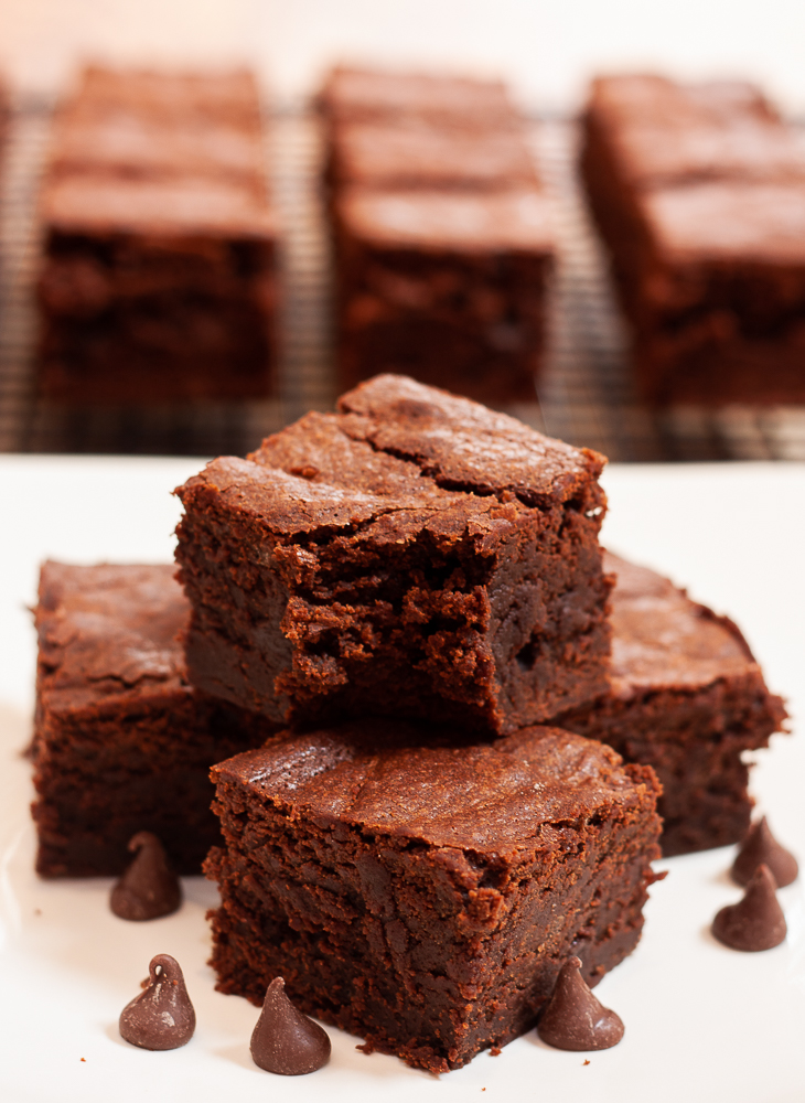 Stack of homemade brownies with brownies on a cooling rack in the background