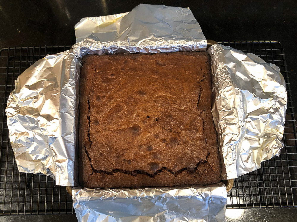 Baked brownies in a pan lined with aluminum foil