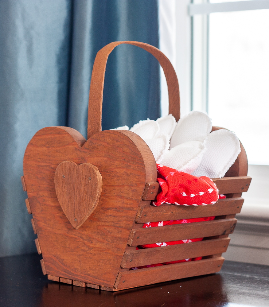Handmade 1980s wood slat basket with a heart filled with handmade white hearts and a red dish towel with hearts