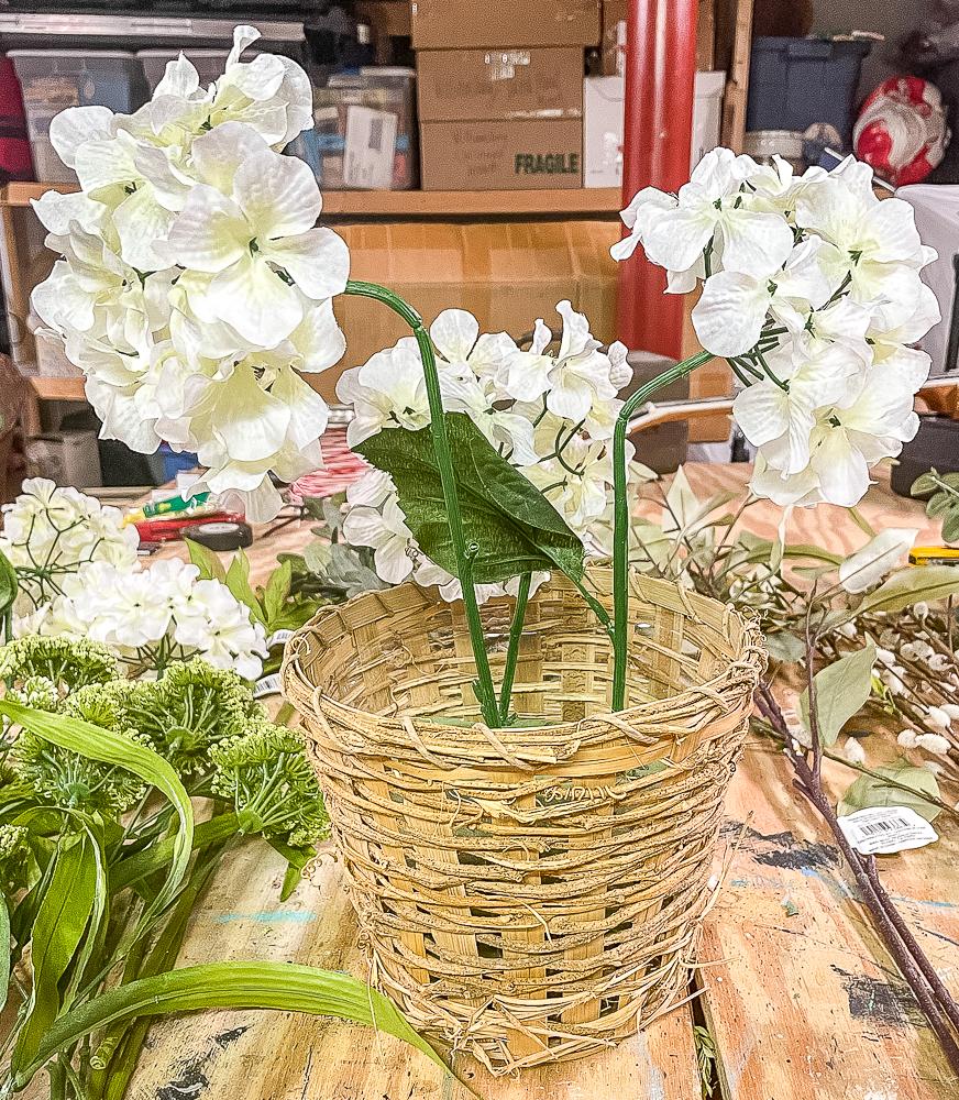 Three faux hydrangea blooms in a woven basket