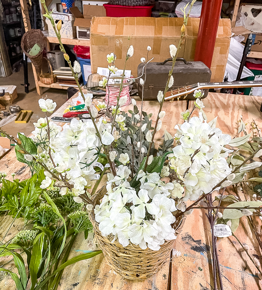 3 hydrangea blooms, pussy willow stems, and flowering apple stems in a woven basket