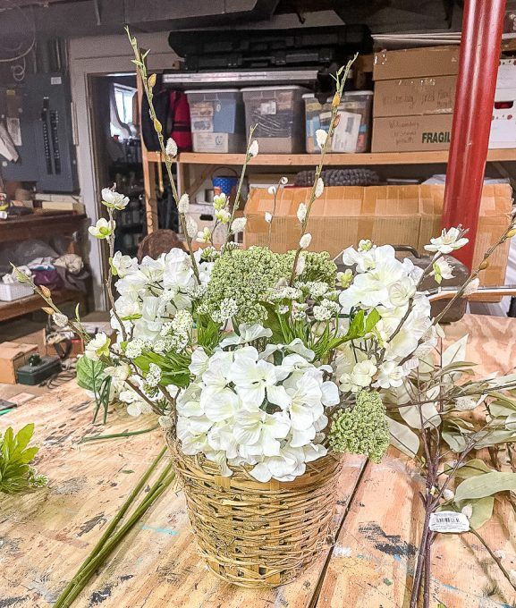3 hydrangea blooms, pussy willow stems, flowering apple stems, and queen anne's lace looking blooms in a woven basket