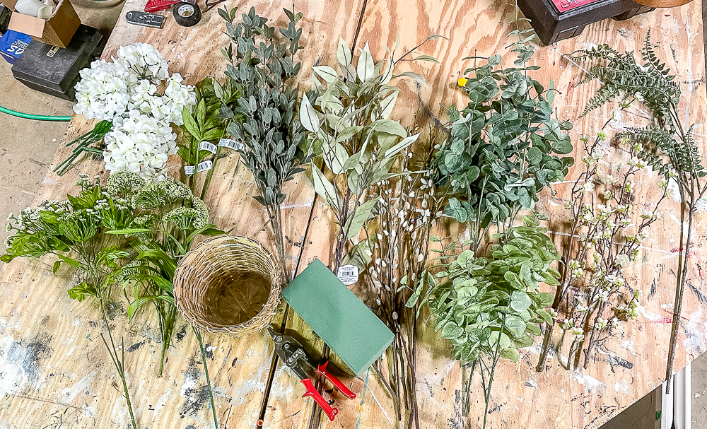 Faux flower stems and greenery on a wood worktop ready to be made into a spring centerpiece