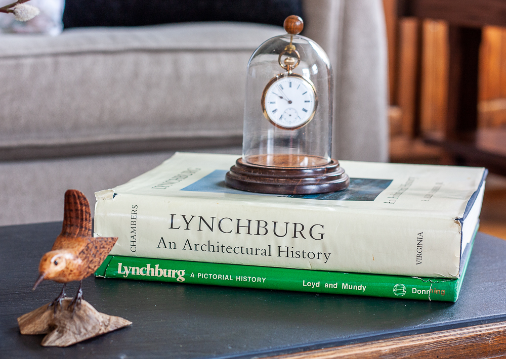 Hand carved bird displayed with S. Allen Chambers Lynchburg an Architectural History book and Lynchburg, A Pictorial History Book and an antique pocket watch