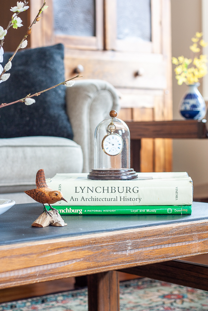 Hand-carved bird displayed with S. Allen Chambers Lynchburg an Architectural History book and Lynchburg, A Pictorial History Book and an antique pocket watch displayed on a 1960s slate topped coffee table