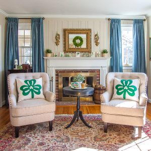 Living room decorated for St. Patrick's Day with Shamrock pillows, green and gold vignettes, green plants and wreaths, and vintage St. Patrick's Day postcards