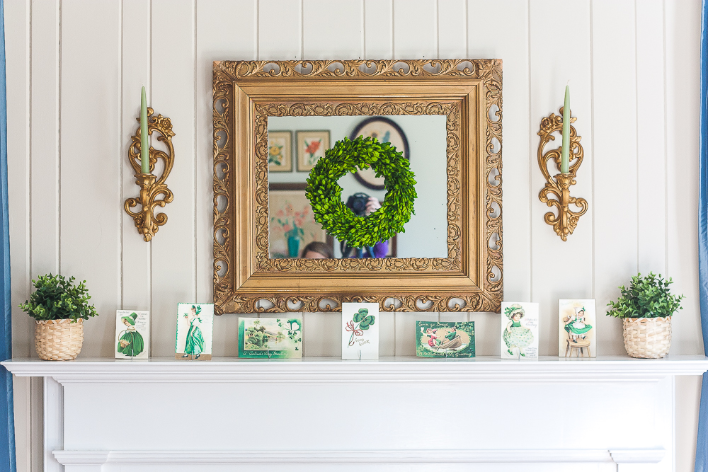 Mantel decorated for St. Patrick's Day with vintage St. Patrick's Day postcards, plants in woven baskets, a boxwood wreath, and green candles.