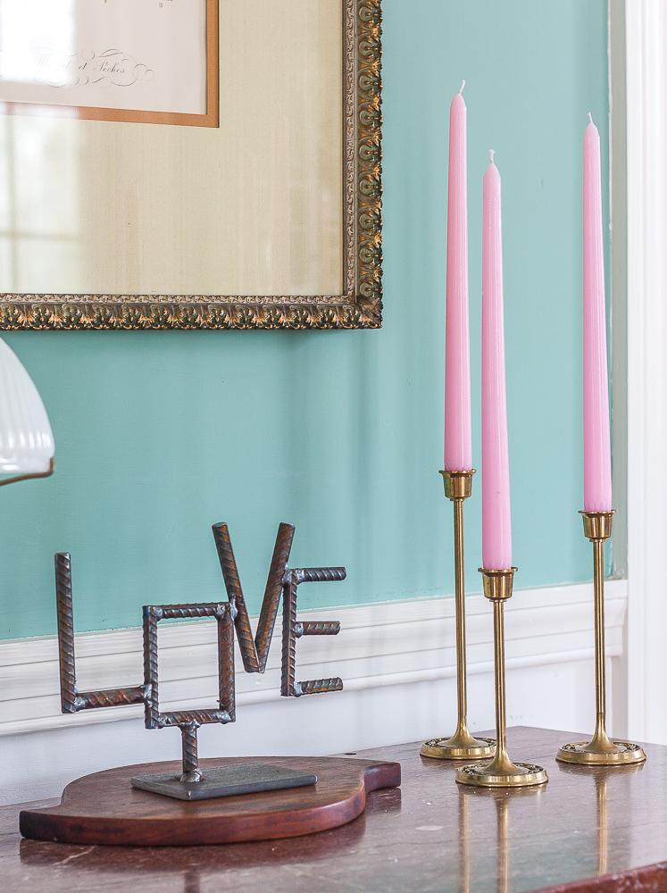 Handmade welded Love sign with trio of brass candlesticks with pink candles