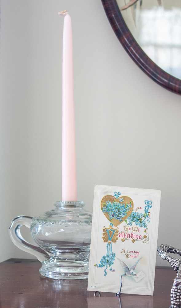 Vintage oil lamp used as a candle holder with a pink candle and an early 1900s Valentine's Day postcard