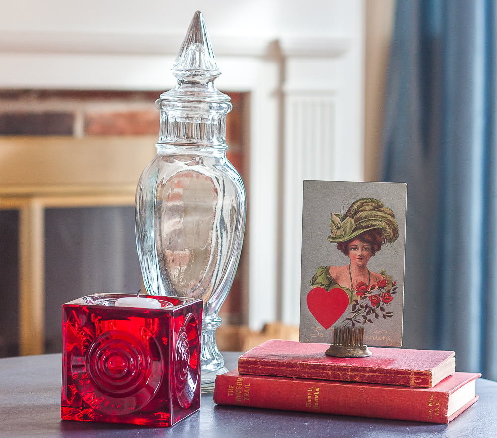 Valentine's Day vignette with a red Blenko candle holder, vintage red books, vintage early 1900s postcard, and a vintage glass candy jar
