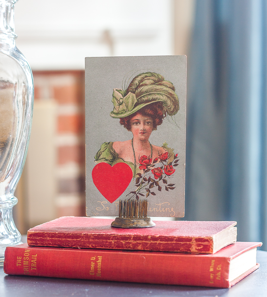 Valentine's Day vignette with vintage red books and a vintage early 1900s postcard.