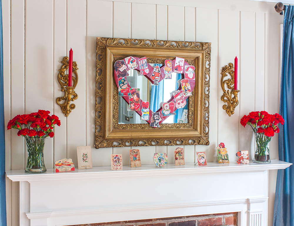 Mantel decorated for Valentine's Day with vintage Valentine's Day cards, red carnations, and red candles