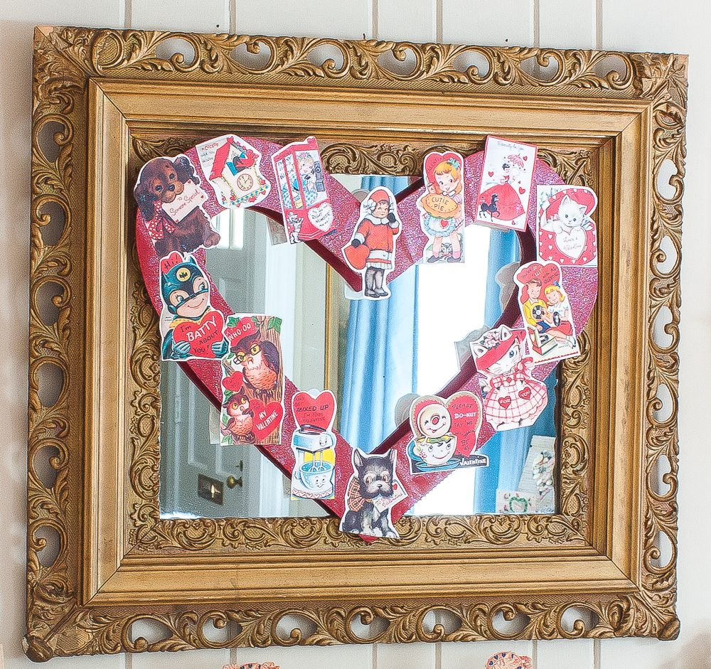 Antique gold mirror with a Valentine's Day wreath decorated with vintage Valentine's Day cards