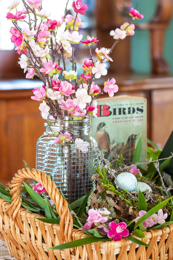 Pink faux florals in a vintage, clear, embossed Mason jar with a bird nest, and 1949 Birds A Golden Nature Guide