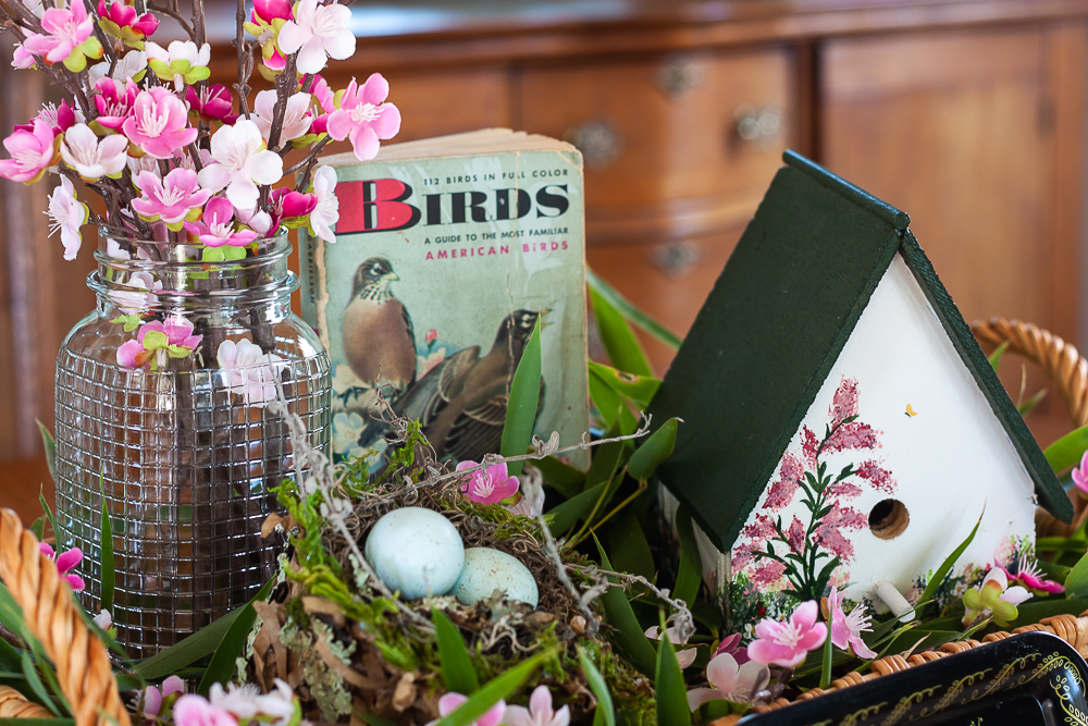 Handmade bird house with a 1949 Birds Golden Nature Guide and pink flowers in a clear, embossed Mason Jar