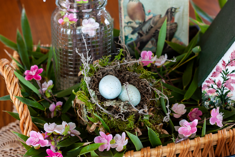 Bird themed spring centerpiece with a bird house, bird book, nest with eggs, and a Mason jar filled with pink flowers