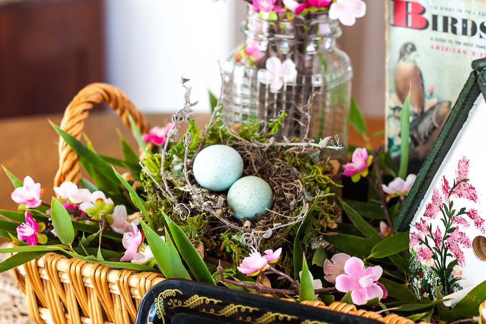 Handmade bird house with a 1949 Birds Golden Nature Guide, birds nest, and pink flowers in a clear, embossed Mason jar