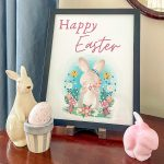 Happy Easter printable in a black frame with a pink Fenton rabbit and a cream rabbit holding a basket that holds an egg