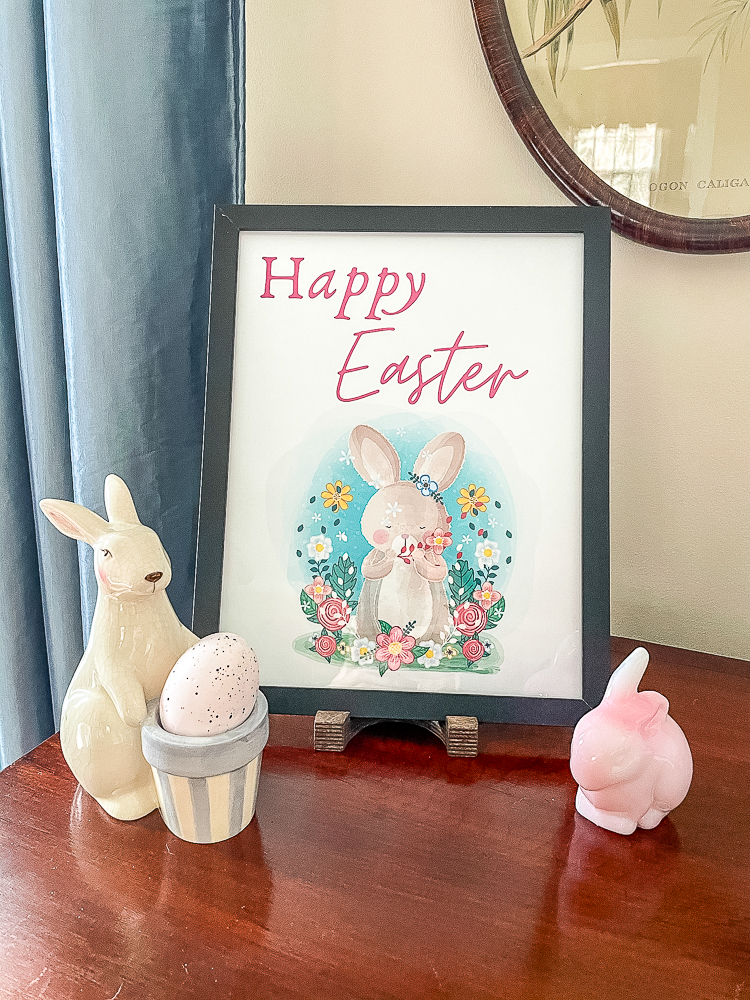 Happy Easter printable in a black frame with a pink Fenton rabbit and a ceramic rabbit holding a basket that holds an egg