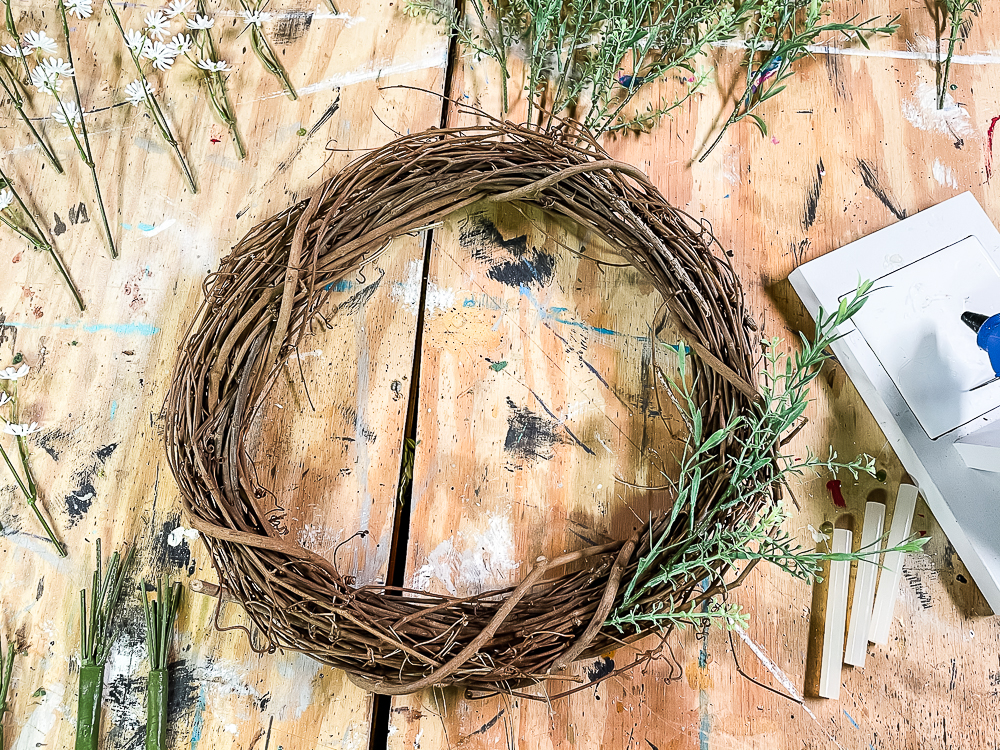 Grapevine wreath with two sprigs of faux spring greenery