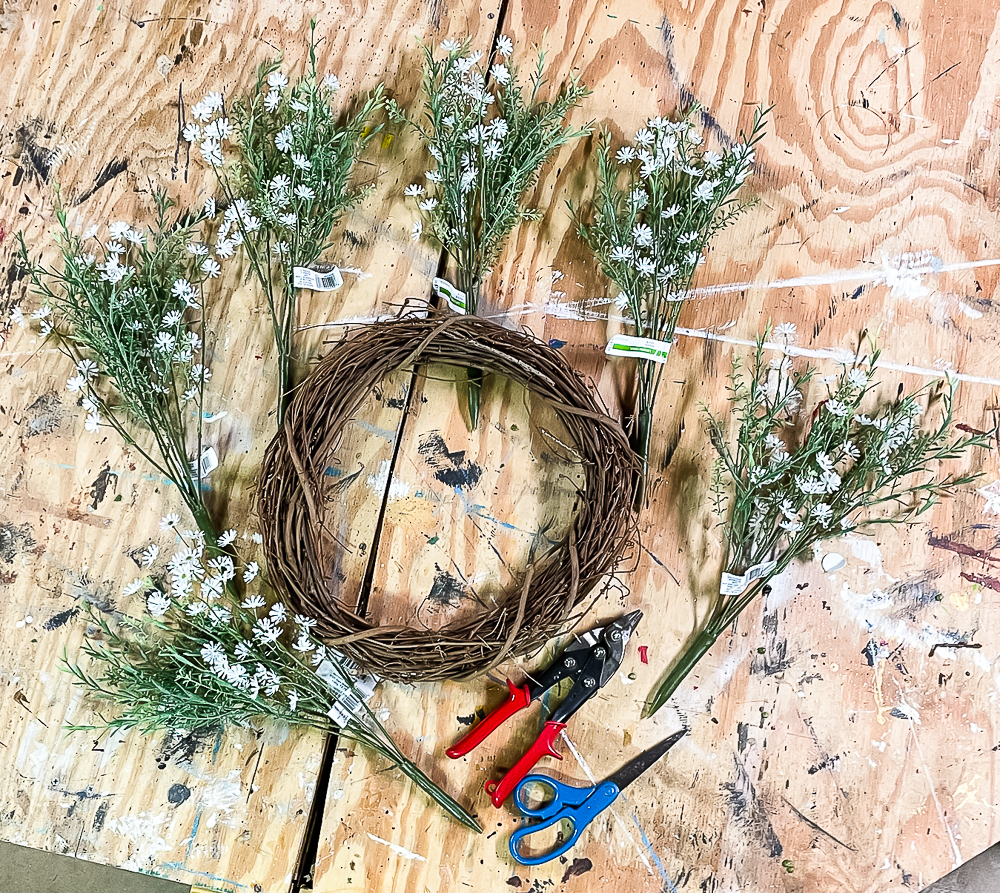 Grapevine wreath, faux florals, tin snips, scissors on a workbench