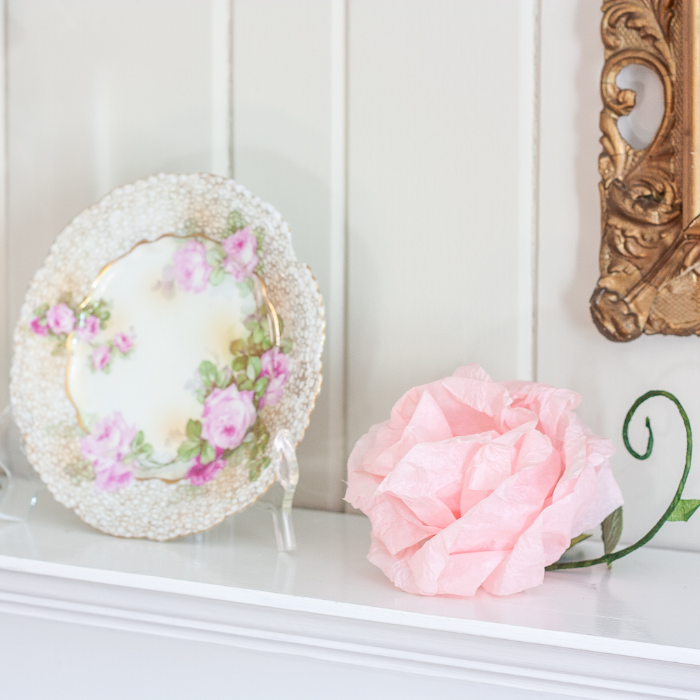 Pink crepe paper flower with a green stem and faux leaf and a plate with roses and gold pattern on the edge
