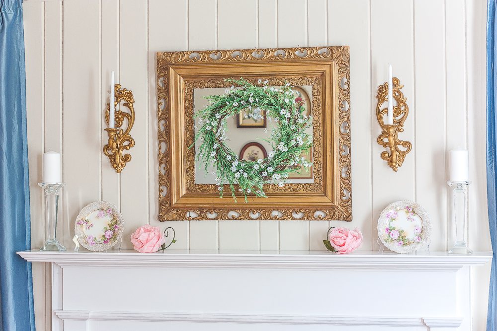 Gold mirror with a green and white wreath, gold sconces with white candles, floral plates, pink crepe paper flowers, and crystal candle holders with white candles.
