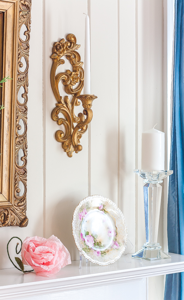 Spring mantel with a gold mirror and sconce, pink crepe paper flower, floral plate, and a Lamps Plus crystal candle holder with a white candle