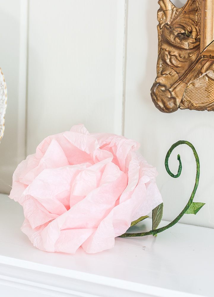 Pink crepe paper flower with a green stem and faux leaf