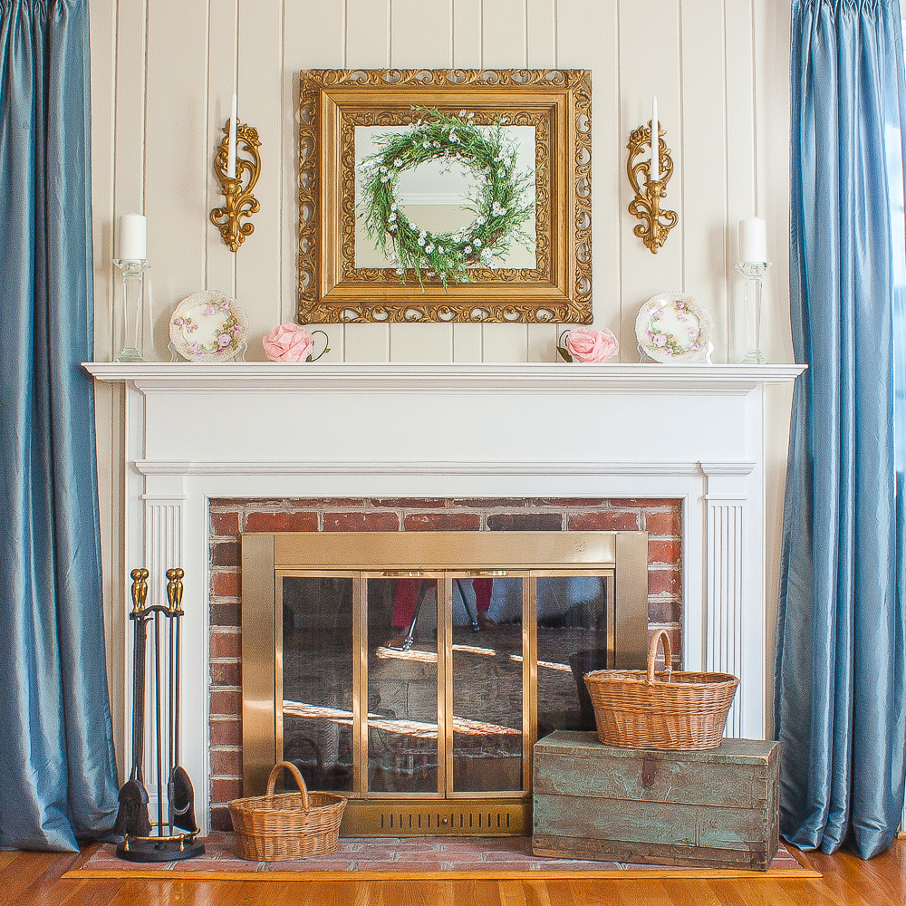 Mantel decorated for spring with pink flowers, a green wreath, white candles, and baskets on the fireplace hearth.