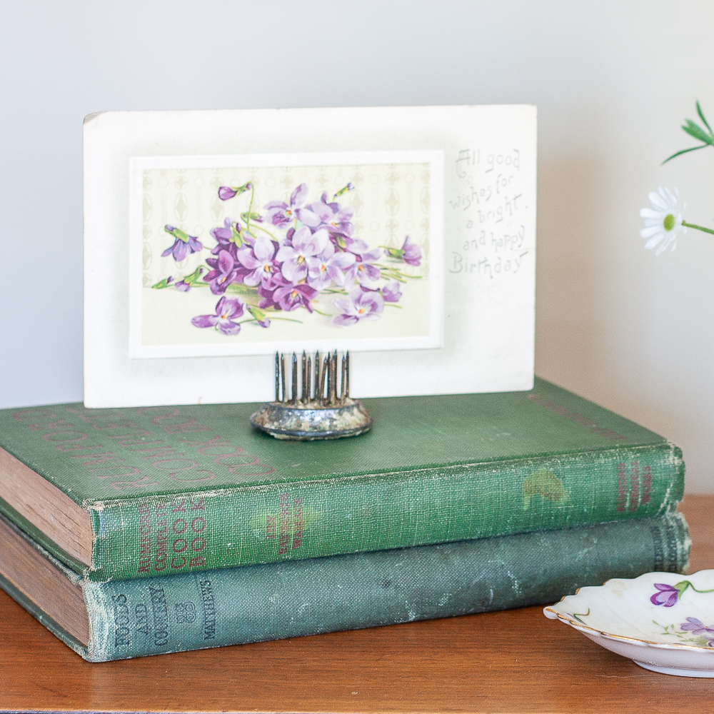 Early 1900s violet postcard displayed on top of two antique books