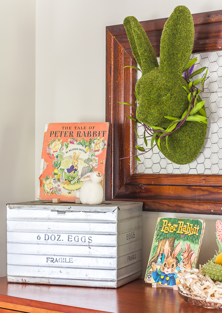 Moss covered rabbit hanging on a frame with chicken wire, 1942 and 1961 Peter rabbit books, and an antique egg shipping crate