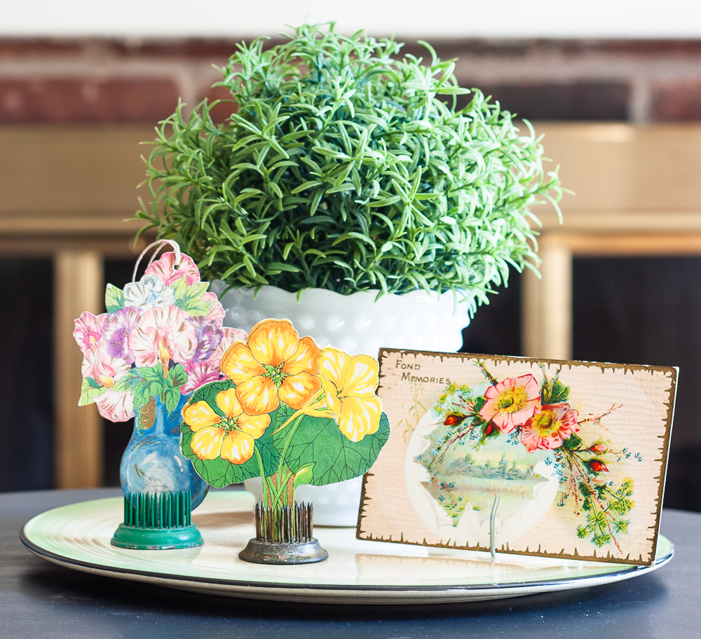 Spring vignette with a faux plant in a milk glass pot, vintage bridge tally cards, and a postcard from the early 1900s