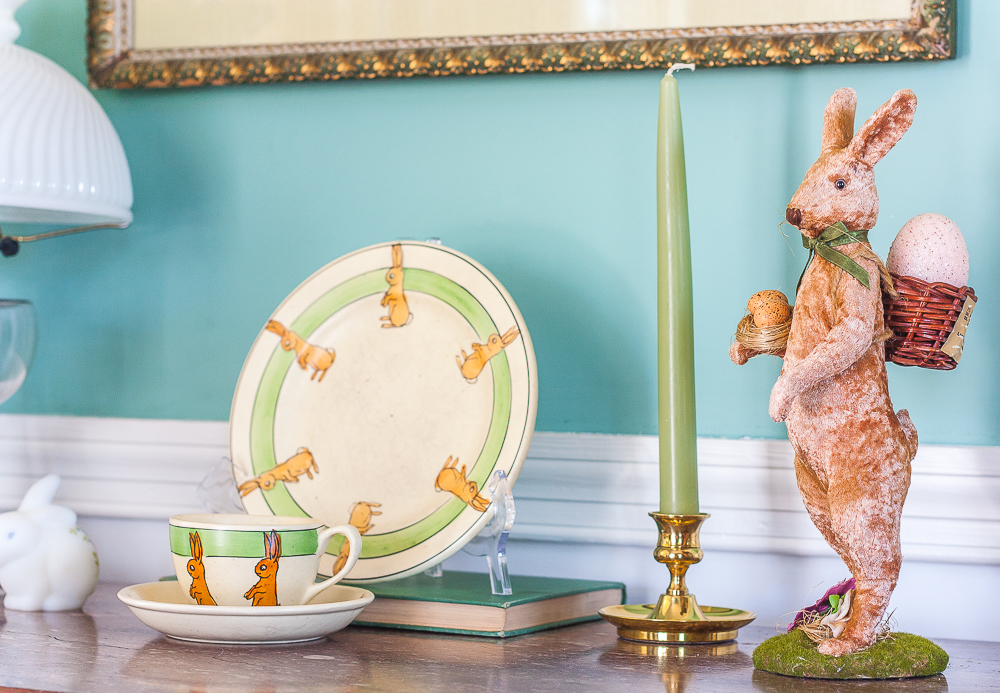 Roseville pottery 1920s juvenile rabbit cup and saucer and matching bunny plate with a Fenton glass rabbit, brass candle holder with a green candle, and a velveteen bunny