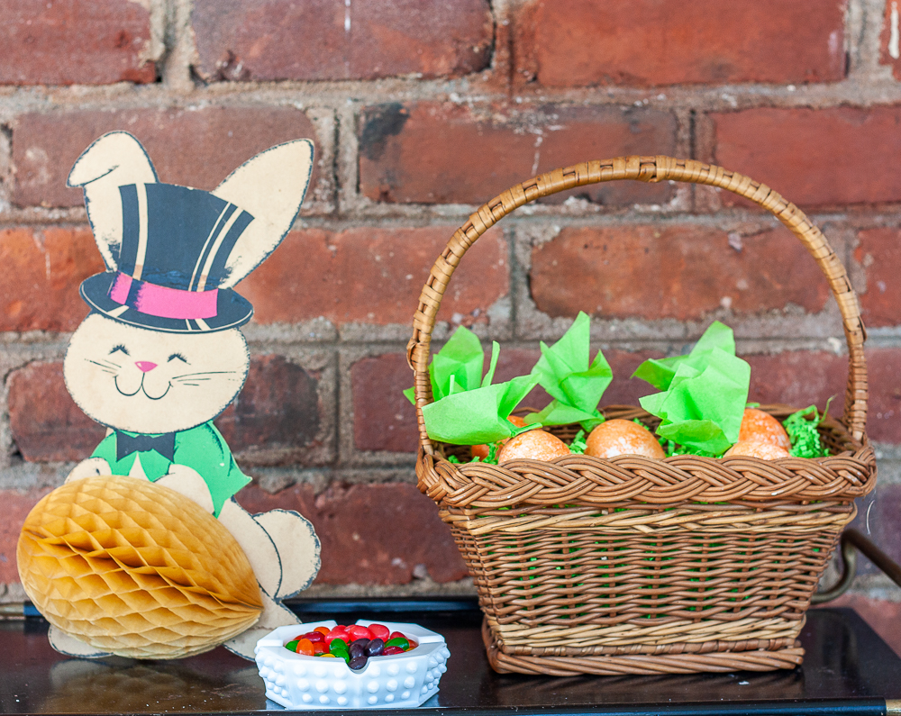 1960 paper rabbit with a fold out egg, milk glass ashtray filled with jellybeans, basket filed with carrot Easter eggs