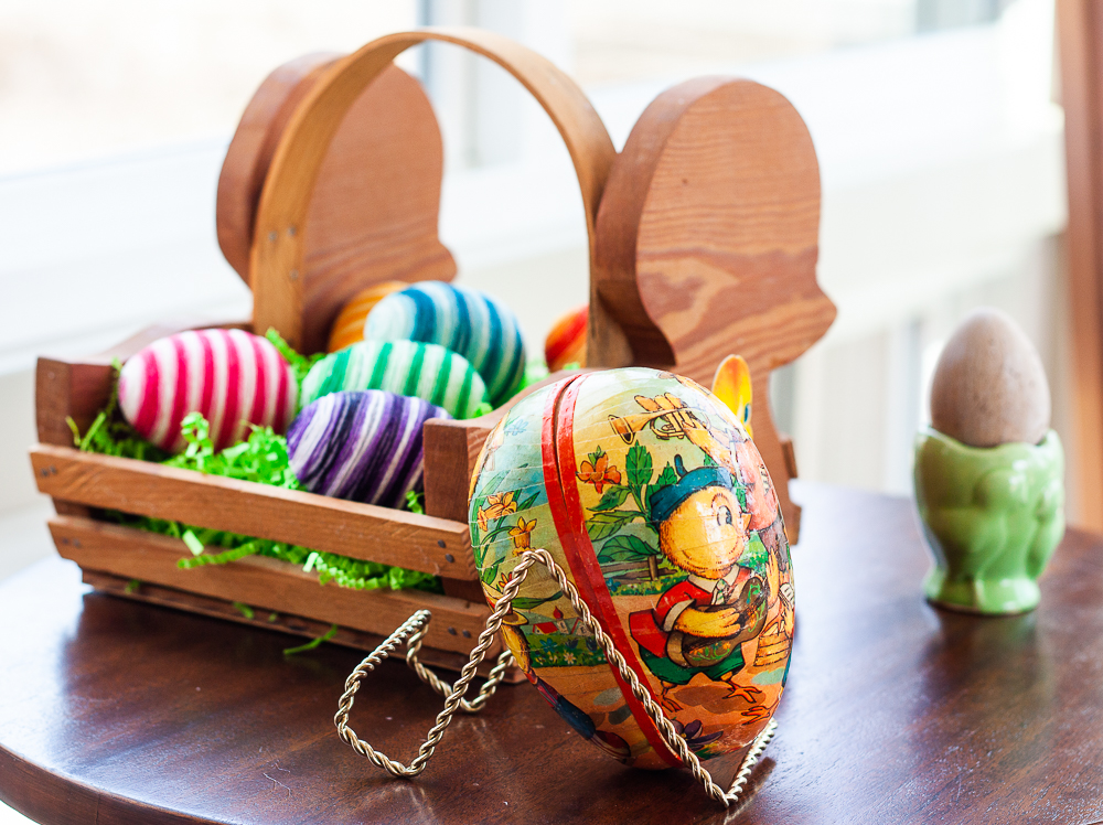 1970s paper egg with wood basket that looks like a chick filled with Easter eggs decorated with embroidery floss