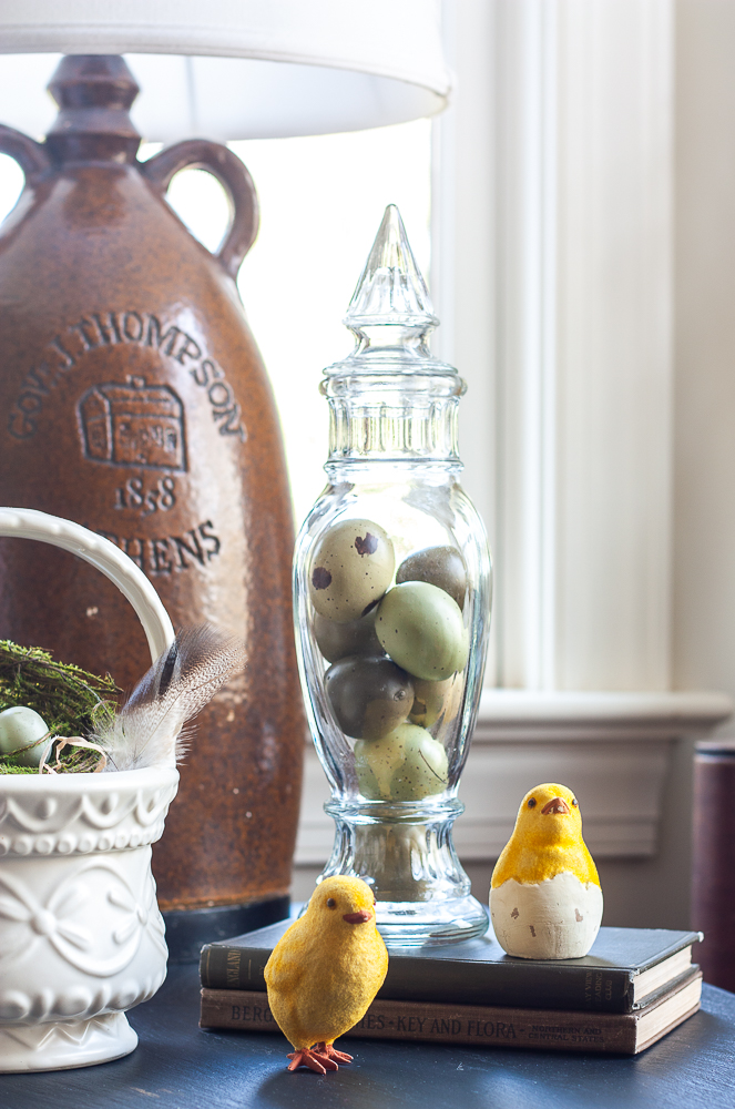 Vintage glass lidded candy holder filled with faux eggs, two chicks, two antique books