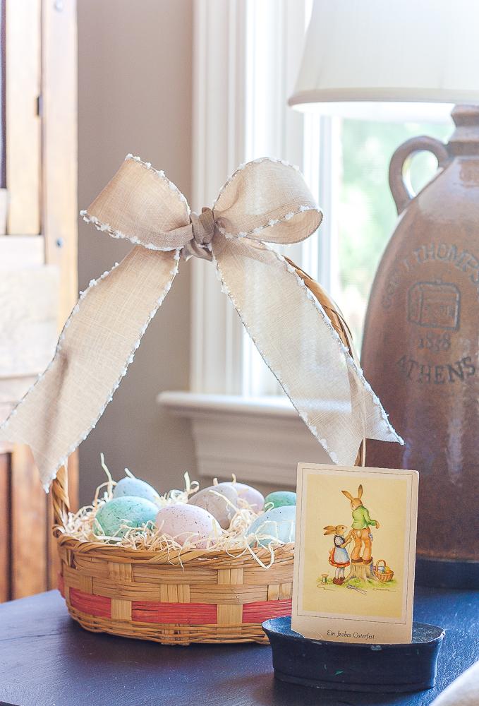 Vintage Easter basket filled with speckle painted eggs and a vintage German postcard